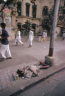 Calcutta, India. A child beggar sleeps on the street - Child labor as seen around the world between 1979 and 1980 - Photographer Jean Pierre Laffont, touched by the suffering of child workers, chronicled their plight in 12 countries over the course of one year.  Laffont was awarded The World Press Award and Madeline Ross Award among many others for his work.