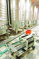 Stainless steel fermentation and storage tanks with cooling coils on the outside. Plate cellulose filter in the foreground. Kantina Miqesia or Medaur winery, Koplik. Albania, Balkan, Europe.