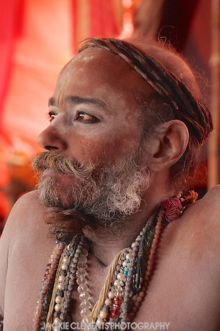 A Naga sadhu of the Juna Akhara with many colourful mala beads and his few remaining dreadlocks twisted around his head.