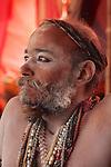 A Naga sadhu of the Juna Akhara with many colourful mala beads and his few remaining dreadlocks twisted around his head.