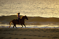 Woman horseback riding along the waters off sunset beach, Oahu