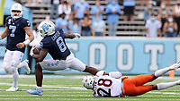 CHAPEL HILL, NC - OCTOBER 10: Michael Carter #8 of North Carolina is tackled by Jermaine Waller #28 of Virginia Tech after a 13-yard run during a game between Virginia Tech and North Carolina at Kenan Memorial Stadium on October 10, 2020 in Chapel Hill, North Carolina.