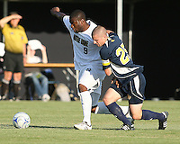Bright Dike #9 of the University of Notre Dame struggles to get away from Daniel Gray #25 of the University of Michigan during a men's NCAA match at the new Alumni Stadium on September 1 2009 in South Bend, Indiana. Notre Dame won 5-0.