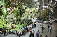 Spain. Province of Madrid. Madrid. Atocha Station (Estación de Atocha) is the largest railway station in Madrid. The station was Madrid's first railway station. It was inaugurated on 9 February 1851 under the name Estación de Mediodía. The old building was taken out of service in 1992 and converted into a 4,000 square meters covered tropical garden. People seat on the public benches. Palm trees. © 2007  Didier Ruef