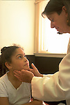 doctor examining glands in throat of smiling young girl