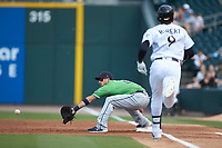 Sean Kazmar Jr. (4) of the Gwinnett Braves reaches for a throw as Luis Robert (9) of the Charlotte Knights hustles towards first base at BB&T BallPark on July 14, 2019 in Charlotte, North Carolina.  The Stripers defeated the Knights 5-4. (Brian Westerholt/Four Seam Images)