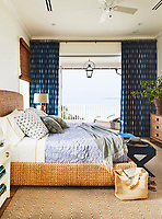 The white bedroom has floor to ceiling blue and white pattern curtains at the sliding doors, which open out on to a terrace. The woven bed, rug and blind of natural materials lend texture to the room.