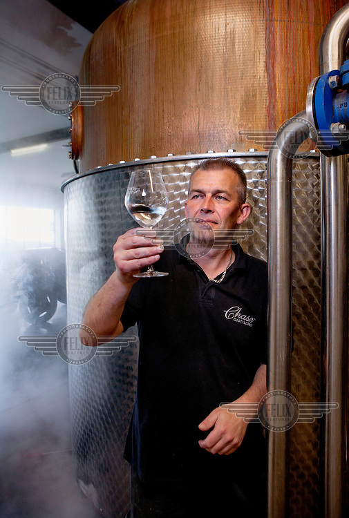 Jamie Baggott, the Master Distiller at the Chase Distillery, examines a glass of spirits at their Rosemaund Farm premises near the city of Hereford.