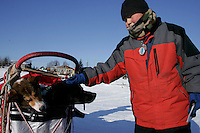 "Tuesday March 6, 2007   Nikolai resident Greg Tony pets ""Burt"" one of Ramy Brooks' dogs  as it sits in the sled bag with teammate ""Skittles"" at the Nikolai checkpoint on Tuesday.  Burt and Skittles were injured on the run from Rohn forcing Ramy to haul them the rest of the way and then drop them both at Nikolai."