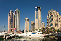 Dubai.  Luxury motor cruisers moored at Dubai Marina with apartment tower blocks in the background..