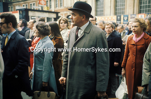 City gent in bowler hat and rolled umbrella.  Waterloo main line train station 1972. Evening rush hour train commuters wait for information due to delays. London England.