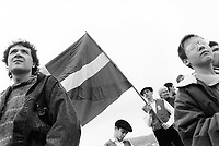 """Spain. Basque Country. Hondarribia (Spanish: Fuenterrabía; French: Fontarrabie) is a town in Gipuzkoa, Province. A teenager holds the ikurrina flag during Aberri Eguna. The ikurrina flag (in Basque) or ikurriña (Spanish spelling of the Basque term) is a Basque symbol and the official flag of the Basque Country Autonomous Community of Spain. This flag consists of a white cross over a green saltire on a red field. Aberri Eguna (""""Fatherland Day"""") which is a celebration day and set of meetings coinciding with Easter Sunday organized mainly by the Basque nationalist movement. It has since become the unofficial Basque national holiday. A group of boys wear traditional costumes and basque berets. A beret is a soft, round, flat-crowned cap, usually of woven, hand-knitted wool, crocheted cotton, wool felt, or acrylic fibre. The Basque Country (Euskadi, País Vasco, Pays Basque), officially the Basque Autonomous Community (Euskal Autonomia Erkidegoa, Comunidad Autónoma Vasca, CAV) is an autonomous community in northern Spain. It includes the Basque provinces of Álava, Biscay, and Gipuzkoa. The Basque Country or Basque Autonomous Community was granted the status of nationality within Spain, attributed by the Spanish Constitution of 1978. The autonomous community is based on the Statute of Autonomy of the Basque Country, a foundational legal document providing the framework for the development of the Basque people on Spanish soil. 21.04.92 © 1992 Didier Ruef"""