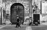 Donna cinese transita davanti ad un portone posto di fronte alla Basilica di Santa Croce. Sulla detra si nota una vecchia Vespa.