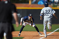 Queens Royals first baseman Drake Harris (23) fields a throw as Levi Perrell (22) of the Catawba Indians hustles down the line during game two of a double-header at Tuckaseegee Dream Fields on March 26, 2021 in Kannapolis, North Carolina. (Brian Westerholt/Four Seam Images)