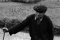 Village d'Arguenos (Haute-Garonne). 10 janvier 1978. Plan moyen d'un vieil homme (vue de face), a une béret sur la tête et s'appuie sur un baton ; en arrière-plan champs.