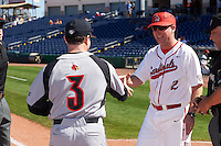 Ball State Cardinals head coach Rich Maloney (2) shakes hands with Dan McDonnell (3) as umpire Ray Parrish looks on during the lineup exchange before a game against the Louisville Cardinals on February 19, 2017 at Spectrum Field in Clearwater, Florida.  Louisville defeated Ball State 10-4.  (Mike Janes/Four Seam Images)