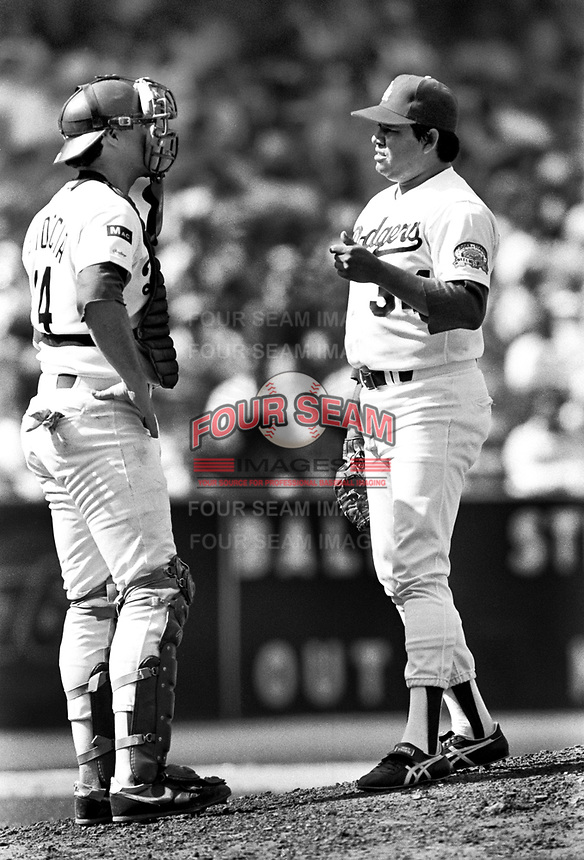 Los Angeles Dodgers catcher Mike Scioscia #14 and pitcher Fernando Valenzuela #34 during a game against the New York Mets at Dodger Stadium during the 1987 season in Los Angeles,California.(Larry Goren/Four Seam Images)