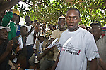 "After successfully showing his peers how to properly use a condom, a volunteer from the crowd receives a t-shirt that states, ""Without a condom, with me, there is no means!""   This peer education session for transport workers was organized by Population Services International at Kilometre 36, 36 kilometers from Conakry, Guinea.    Transport workers are a high-risk group for HIV/AIDS due to the amount of time they spend away from home."