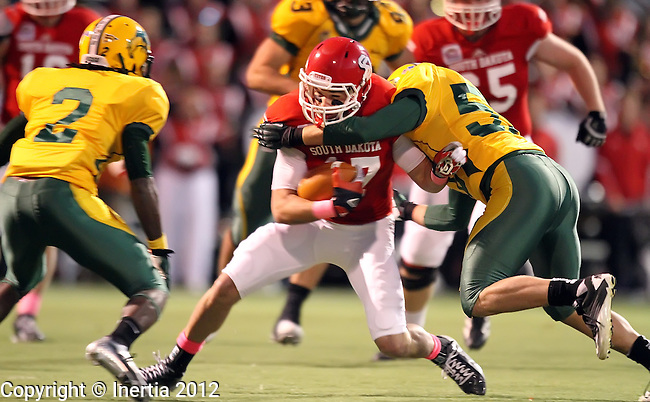 SIOUX FALLS, SD - OCTOBER 20:  Will Powell #17 from the University of South Dakota is brought down by Brendin Pierre #2 and Travis Beck #52 from North Dakota State University in the first quarter of their game Saturday night at Howard Wood Field.  (Photo by Dave Eggen/Inertia)