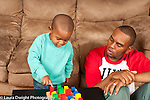 Two year old toddler boy with father shapes puzzle child pointing and talking as he identifies colors