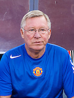 Manchester United head coach Sir Alex Ferguson watches his team from the bench before the friendly at FedEX Field in Landover, MD.  Manchester United defeated FC Barcelona, 2-1.