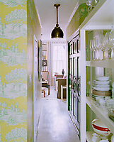 The dramatic backdrop of an acid-coloured toile de Jouy wallpaper leads from the kitchen to the entrance hall and on into the living room