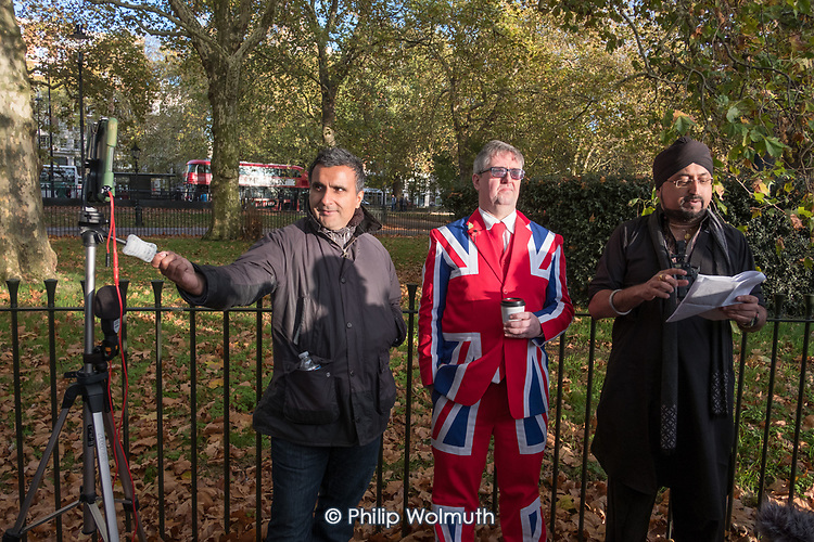 Man in a Union Jack suit with Free Speech advocate Raj and a videographer, Speakers' Corner, Hyde Park, London.