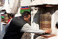 Bodhnath, Nepal.  Buddhist Worshiper Turning Prayer Wheel.