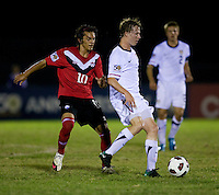 Matthew Dunn (5) of the United States passes the ball away from Keven Aleman (10) of Canada during the finals of the CONCACAF Men's Under 17 Championship at Catherine Hall Stadium in Montego Bay, Jamaica. The United States defeated Canada, 3-0, in overtime