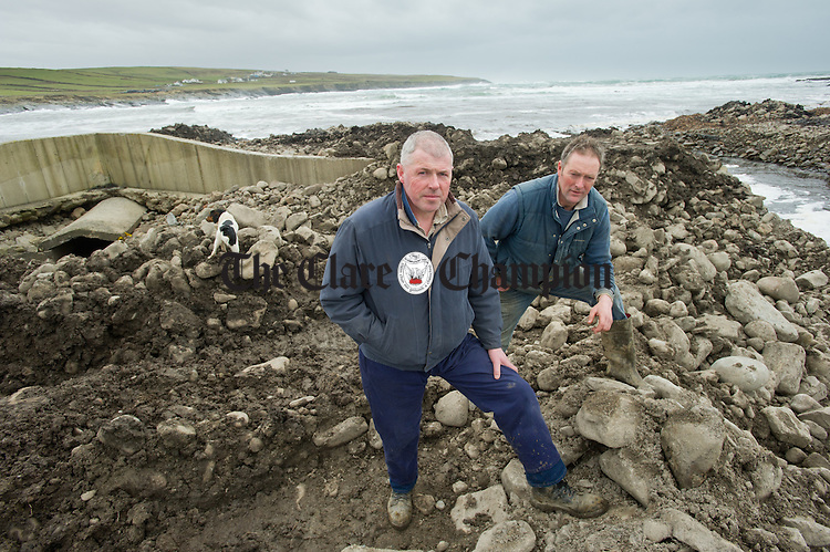 Locals; Tomas Flanagan and Gearoid Greene examine the extent of the recent damage to the sluice on their farms at Farrihy Bay. Photograph by John Kelly.