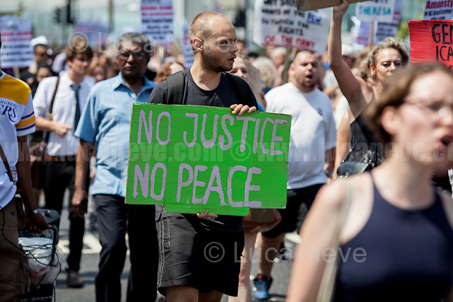 """London, 21/06/2017. Today, on London's hottest day of the year - with temperature picks over 30 degrees Celsius - """"Movement for Justice By Any Means Necessary"""" (MFJ) and members of the public marched from Shepherd's Bush to the Houses of Parliament (""""Total length of the route is 5.56 miles""""- Source: MFJ) to protest against the newly elected minority Conservative Government led by the former Secretary of State, Theresa May, to call for immediate rehousing of the residents of the Grenfell Tower, and to grant """"amnesty and permanent UK residency for those without immigration papers"""" (Source - The Guardian.com). The march was one of the several other protests held on the so called """"Day of Rage"""" coinciding with the state opening of the Parliament by HM Queen Elizabeth II. The MET Police arrested one protester who was released in the evening without charges.  <br /> <br /> For more information please click here: https://www.facebook.com/events/1490621807662608/ & http://www.movementforjustice.org/ & https://twitter.com/followMFJ<br /> <br /> For my reportage: """"14.06.2017 - Fire at Grenfell Tower - Aftermath of a Disaster"""" please click here: http://bit.ly/2rESn90"""