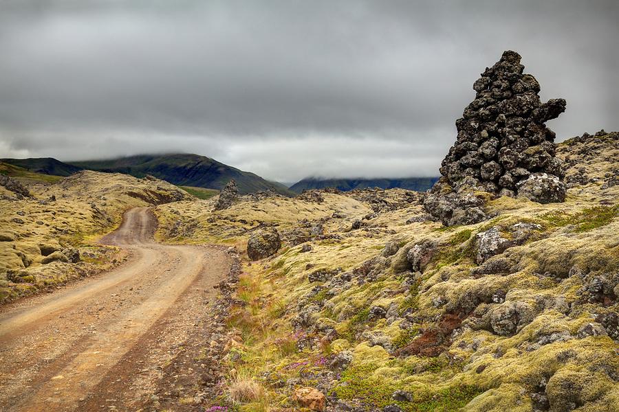 Dirt road through green moss covered Berserkjahraun lava flow and cairn, Snaefellsnes peninsula, West Iceland, Iceland