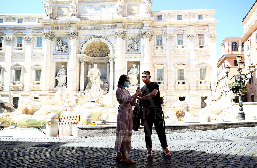 People stand in front of Fontana di Trevi in central Rome on May 4, 2020 as Italy starts to ease its lockdown, during the countrys lockdown aimed at curbing the spread of the COVID-19 infection, caused by the novel coronavirus.<br /> UPDATE IMAGES PRESS/Isabella Bonotto
