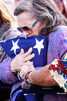 Maxine Edens embraces a flag presented to her by the The Blue Eagles Honor Guard during a Memorial service held for her husband Coach Bennie Eden at the Point Loma High School Football stadium that was recently renamed in his honor, Saturday February 23 2008.