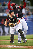 Batavia Muckdogs catcher David Gauntt (46) throws to first base as Javier Lopez (23) avoids a collision during a game against the West Virginia Black Bears on June 28, 2016 at Dwyer Stadium in Batavia, New York.  Batavia defeated West Virginia 3-1.  (Mike Janes/Four Seam Images)