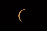 Only a crescent Sun remains in the first partial eclipse phase as the totality phase approaches during the Great American Eclipse on August 21, 2017.  Sunspots are visible on the sun's surface.