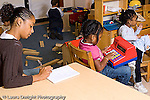Preschool 3-4 year olds female student teacher taking notes in classroom horizontal