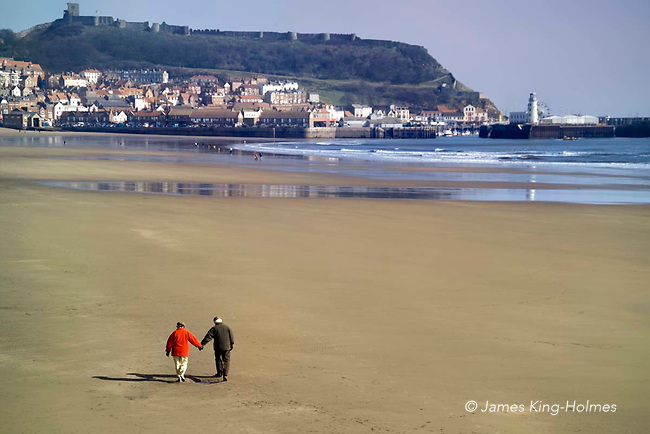 An older man and woman take a walk along a deserted beach in the spring sunshine, even though they have to wrap warmly against the cold wind and exposed location. For older people, walking is a beneficial form of exercise for older people, giving reduced risk of coronary heart disease, strokes, diabetes, hypertension, bowel cancer and osteoporosis.