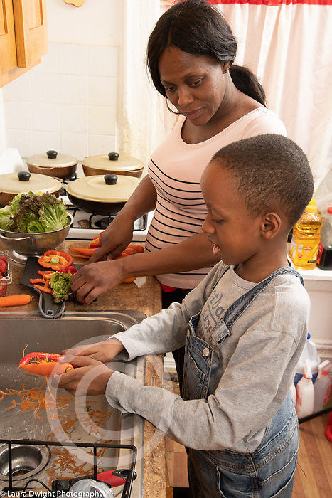 Mother in kitchen with 10 year old son, food preparation, boy peels raw carrot as mother prepares lettuce
