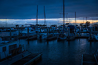 A break in the weather on the horizon behind boats moored at the San Leandro Marina.  The oppressive storm clouds that brought days of rain broke, and below them was a mix of daylight and lighter billowing clouds, mixed with a waning sunset glow.