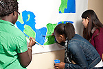 group of high school students painting world peace racial harmony poster in school corridor