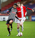 Pars' Faissal El Bakhtaoui and Ayr Utd's Scott McLaughlin challenge for the ball.