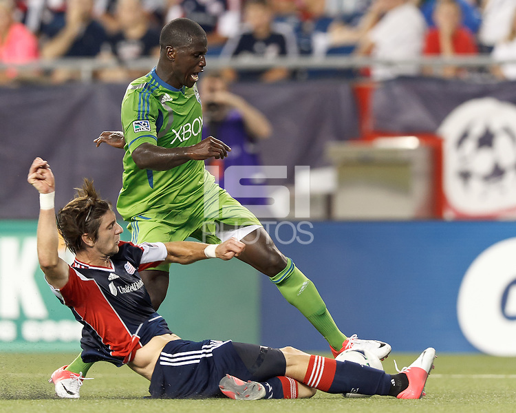 New England Revolution midfielder Stephen McCarthy (26) slide tackles attacking Seattle Sounders FC forward Eddie Johnson (7). In a Major League Soccer (MLS) match, the New England Revolution tied the Seattle Sounders FC, 2-2, at Gillette Stadium on June 30, 2012.