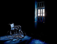 Lone wheelchair by a broken window in an abandoned mental asylum.