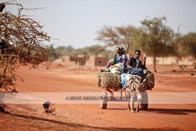 """In West Africa, certain villages have markets that """"assemble"""" at regular intervals, such as weekly or every three days.  People from villages around the region come to Djibo's weekly Wednesday market in northern Burkina Faso to buy and sell food, livestock, and other goods and services.  Here, a family brings harvested millet to market by donkey cart."""