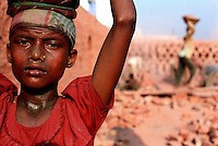 Child carrying bricks on her head in a brick factory.