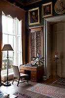 Detail of one corner of the library with one of the built-in bookcases and a desk