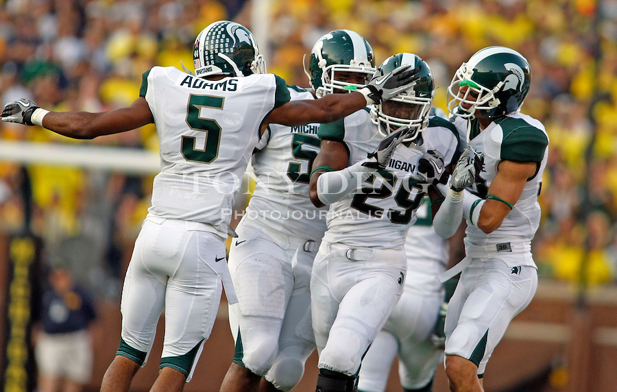Michigan State cornerback Chris L. Rucker (29) is congratulated by cornerback Johnny Adams (5) and teammates after catching an interception in the fourth quarter of an NCAA college football game with Michigan, Saturday, Oct. 9, 2010, in Ann Arbor. Michigan State won 34-17. (AP Photo/Tony Ding)