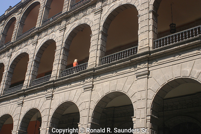 A SMALL DASH of WOMAN's RED COLOR BRINGS LIFE to MEXICO's MULTI-LEVELED CAPITOL BUILDING.