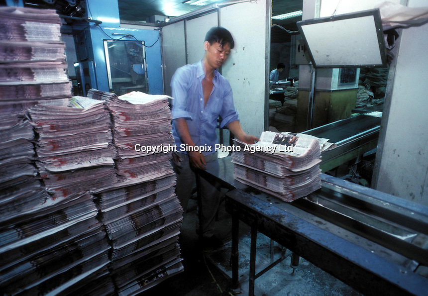 Factory worker works at the newspaper-printing factory in Guangzhou, China..13-JAN-03